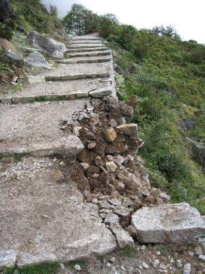Ødeleggelser etter jordskjelvet. Stien har rast ut og kampestener ligger i veien.