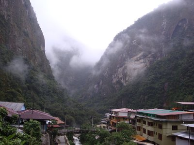 Aguas Calientes. Machu Picchu is to the left behind huge mountain