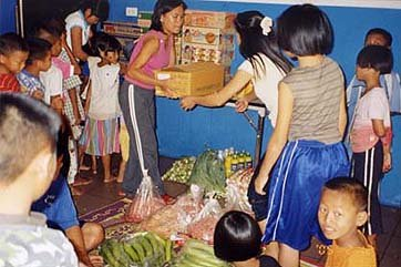Giving food to orphan childrens home near Chiang Mai Thailand