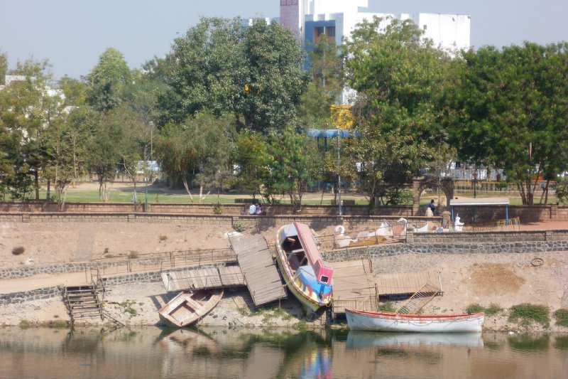 A boat parked precariously on the banks of the Vastrapur Lake