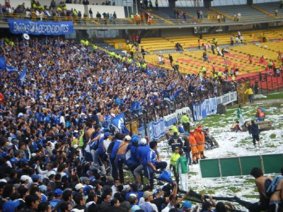 Fans climb on the barriers in celebration