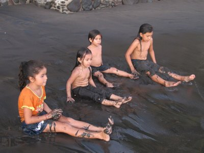 Kids rolling around in the black sand