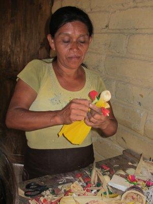 Chorti woman crafting a corn husk doll
