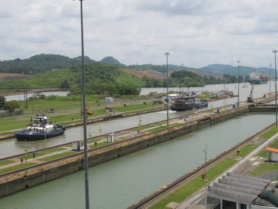 Ships exiting the second stage of locks at the Miraflores Locks.  After the water reaches the same level as the Miraflores lake the gates open and release the boats to a height of 85 feet above sea level