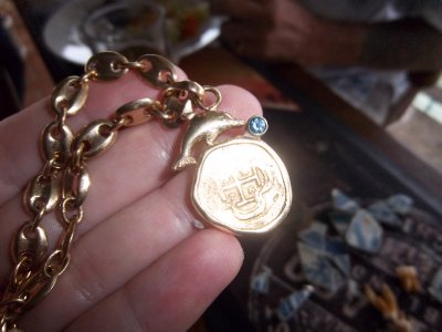 Brian's necklace contains a gold Spanish coin he salvaged and a blue Sapphire from his mining days