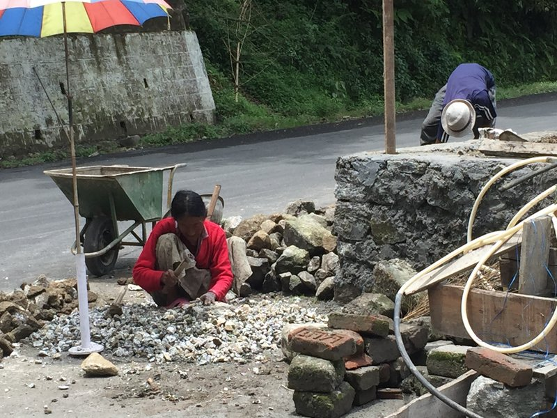 Women breaking stones for road works