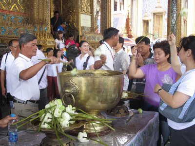 people dipping lotus flowers in holy water, then dropping it on their heads outside temple