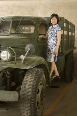 "One of the things I love most about Shanghai is what I call its ""schizophrenia"" - it has an awesome mixture of old and new that coexist side by side.  The SH Film Park was full of picture opportunities where I could show some more of this schizophrenia, for example here, with the beautiful woman in a delicate qi pao standing on the army truck.  The ultimate example of the schizophrenia was in the park itself.  At least one strip of buildings definitely has two personalities - one side is a foreign hospital and faces the lawn with all of the other foreign buildings, while the other side is the shops and buildings on the fake Nanjing Road"