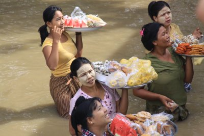 Villagers waist deep in the river eager to sell their wares