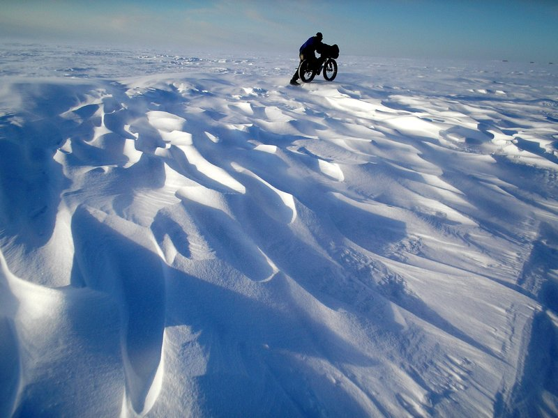 Bill Merchant pushing his bike along the Iditarod Trail near Elim Alaska