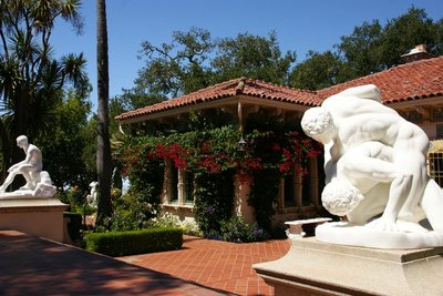 Castle gardens decorated with antient marble statues and flowering bushes, Hearst Castle, California, US