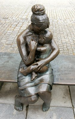 Statue of a young woman holding a baby at the main town square