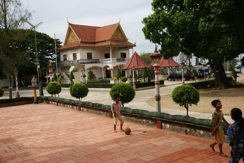 Girls playing football in front of the 100 pillars Sambor pagoda