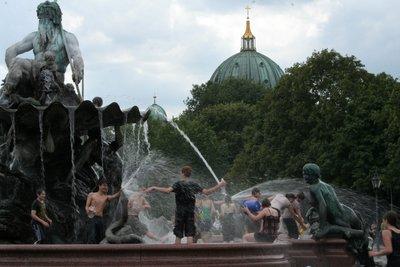 Neptunbrunnen : La fontaine de Neptune. Des gens profitent de cette journée très humide pour faire une grosse bataille d'eau dans la fontaine.