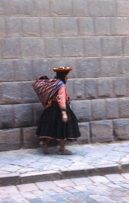 Local Indian woman in front of Inca wall in Cuzco