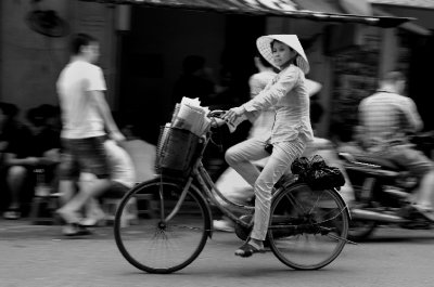 A newspaper seller cycles past a Hanoi café in the city's Old Quarter