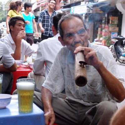 A smoker with his glass of bia hoi at a street café in Hanoi