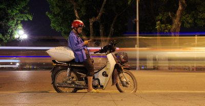 A motorcyclist stops to check his phone on the busy road along Hoan Kiem Lake&#39;s east side