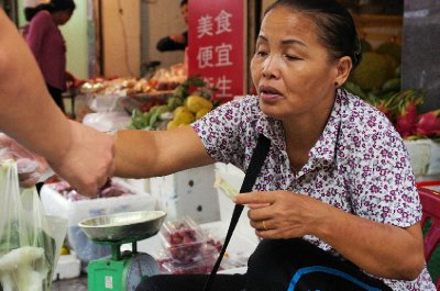 A street vendor completes a sale at one of Hanoi's many food markets