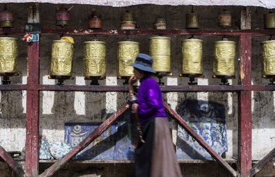 Tibetan lady spinning prayer wheels