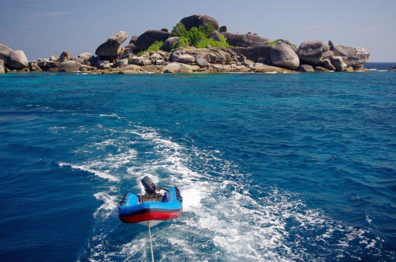 Big rocks, small boat and blue sea