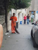 Street sweeper with straw broom.