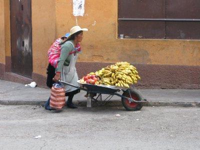 Her jobbes det hardt med baby paa ryggen og en trillebaar full av bananas!