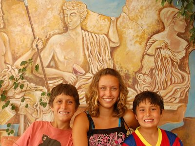 This photo was taken at a restaurant in the old town of Rhodes.  The kids are sitting in front of a modern painting of a Greek classical depiction.