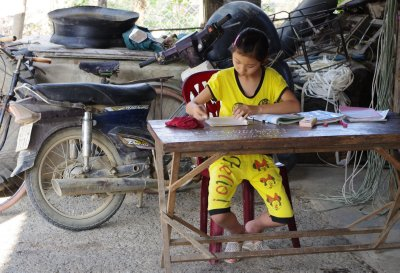 I arrived at our teastop in the Na River Valley to find it deserted, the rest of the group having eaten and left. This girl was studiously doing her homework, oblivious to the cameras!