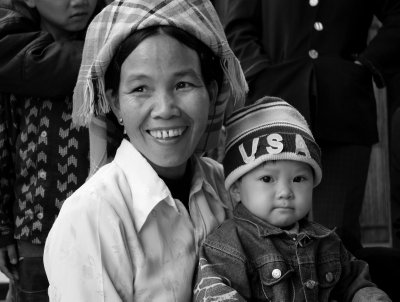 """This mother and baby near Nghia Lo were drawn in to meet us by Phong with the offer of sweets. We got chatting...""""how old are you?"""" she asks, """"31"""" I reply, """"no children?"""" she responds. A familiar refrain!"""
