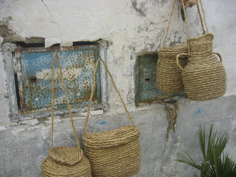old wall displaying baskets being sold
