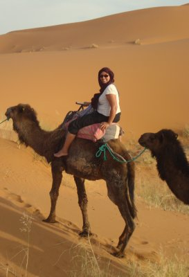 Jennifer and her camel going up a dune in the Sahara Desert