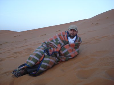 Robert taking in the sunrise in the desert, Merzouga, Morocco.  It's cold in the morning!