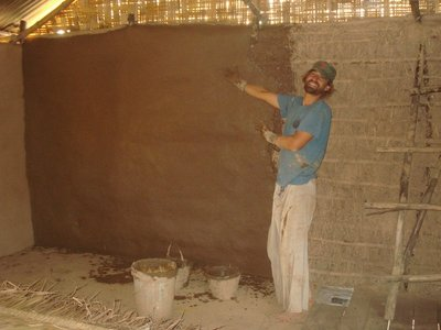 Tim using local materials, including mud from the Mekong River, to build their house