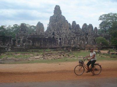 Jennifer biking by Bayon Temple at Angkor Comlex