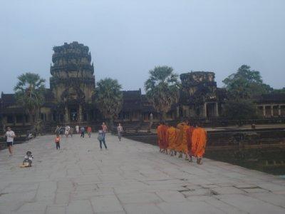 Monks walking along causeway into Angkor Wat after Sunset