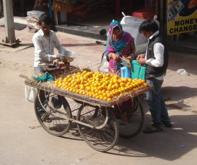 Couple buying oranges in Pahar Ganj, New Delhi