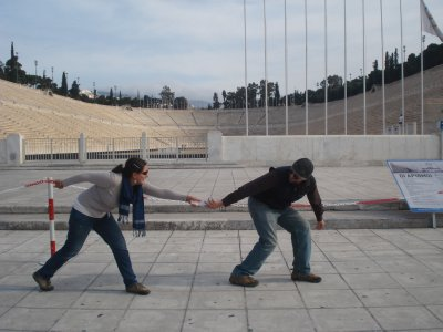 Passing a baton (our map) in front of the Marble Olympic Stadium in Athens.  It was built for the first modern Olympic Games in 1896.