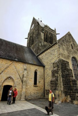 Mere St Eglise- site of an American para assault during D-Day. 1 Para was snagged on the church steeple and played dead for 2 hours with a shot ankle, later captured, later escaped to tell his tale. A dummy with a chute now hang on the steeple permanently
