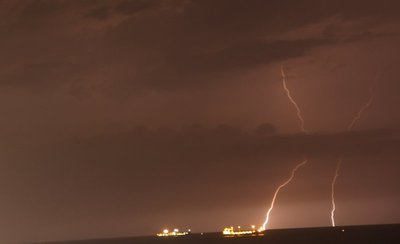 Ships in bay with lightning
