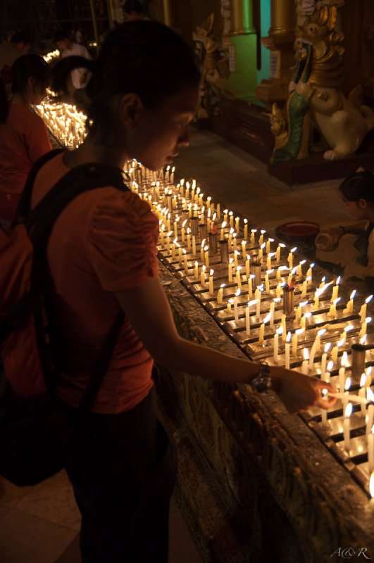 Candle lighting and prayers surround the base of the pagodas