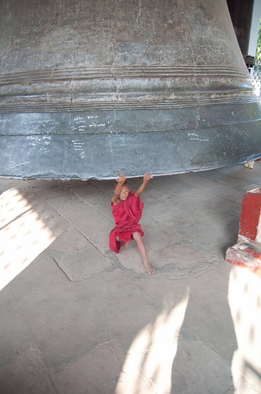 A young monk playing under the Mingun bell, the world's second largest