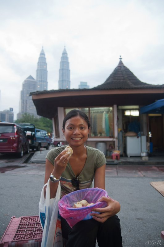 Rina enjoying a bowl full of her favourite fruit, durian, in front of the domineering Petronas Towers