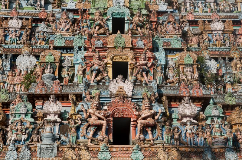 Close up of the façade, complete with moustached gods and scenes of Hindu stories