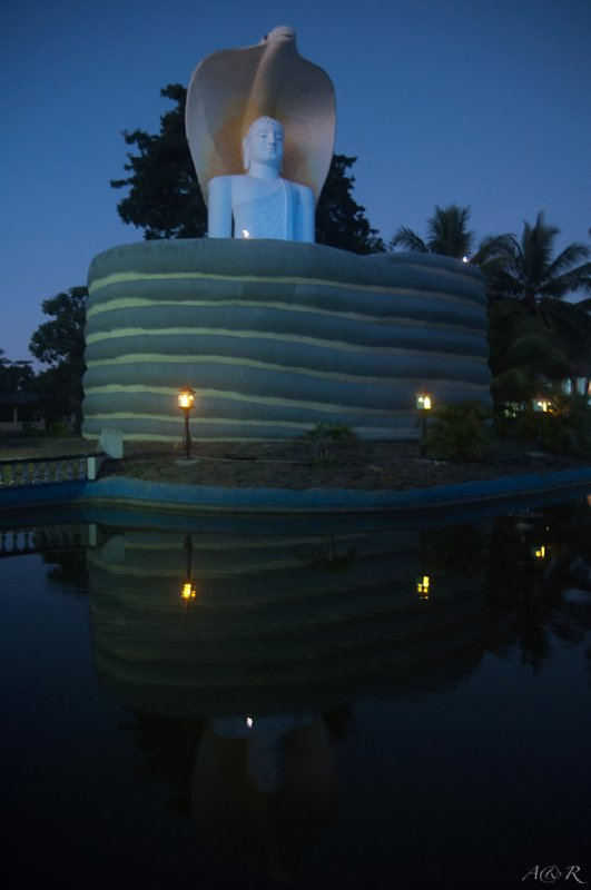 A Buddha attitude encircled by a cobra at dusk in Chilaw