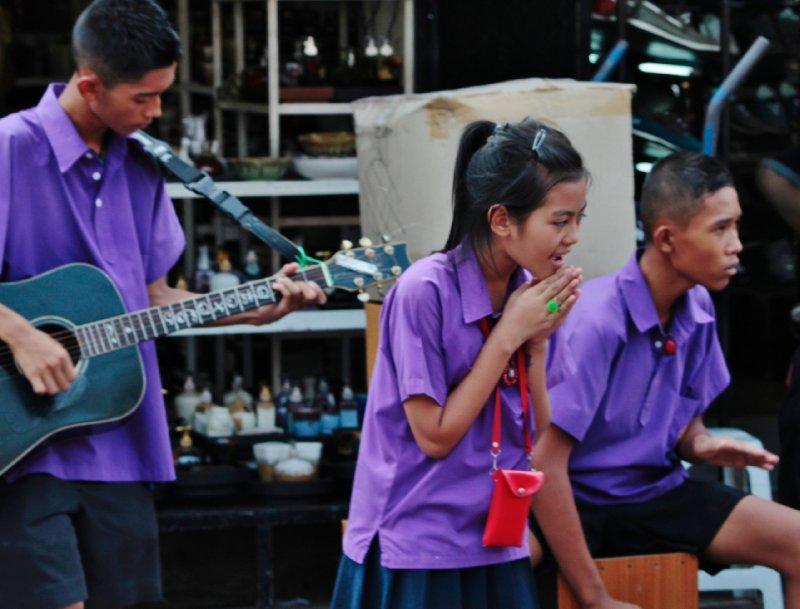 een plaatselijk bandje op de markt met een jonge, vals zingende zangeres