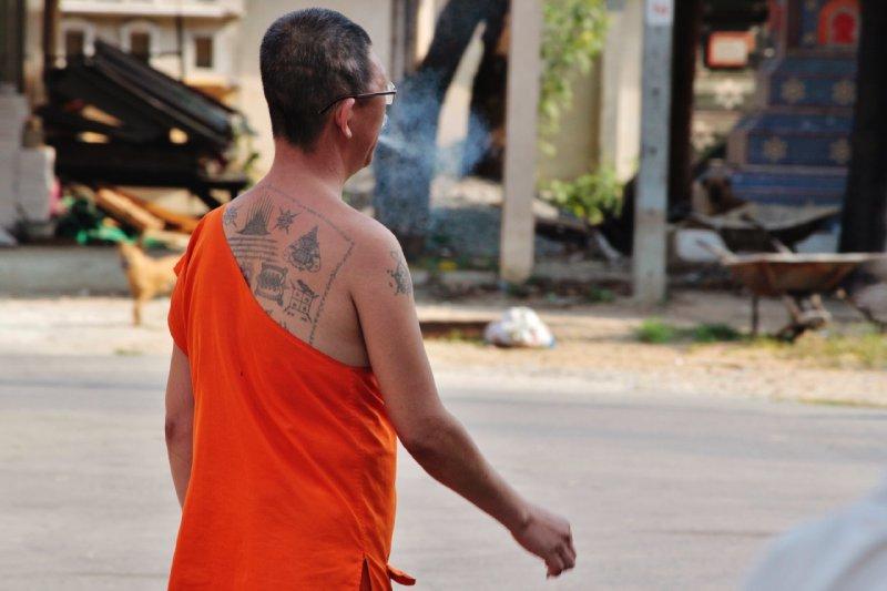 een getatoeëerde monnik met sigaret gespot tijdens onze fietstocht