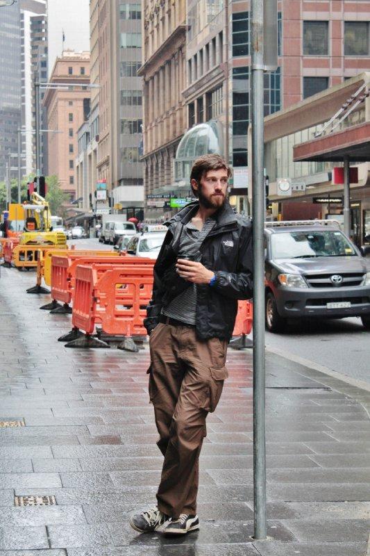 De metropolitan look: 'Sacha nipt van een meeneemkoffie en doet dat met stijl op bruine sneakers draagt hij een donkerbruine travellersbroek met handige zijzakken. Om zich te beschermen tegen de regen koos hij voor een stijlvolle blauwe k-way...'