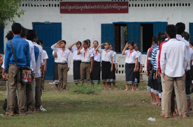 tijdens onze fietstocht waren we getuige van het einde van een schooldag die traditioneel communistisch gewijs wordt afgesloten met het salueren van de Laotiaanse vlag en het zingen van het volkslied