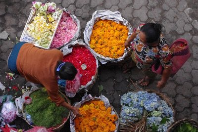 Local shopkeeper buys flower petals for Hindu offering in Ubud market